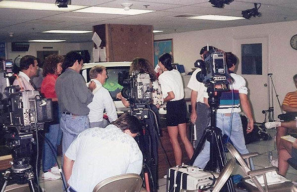 Inside the National Hurricane Center (NHC) near the time of Hurricane Andrew's South Florida landfall on August  24, 1992. Media interviewing NHC Director Bob Sheets.