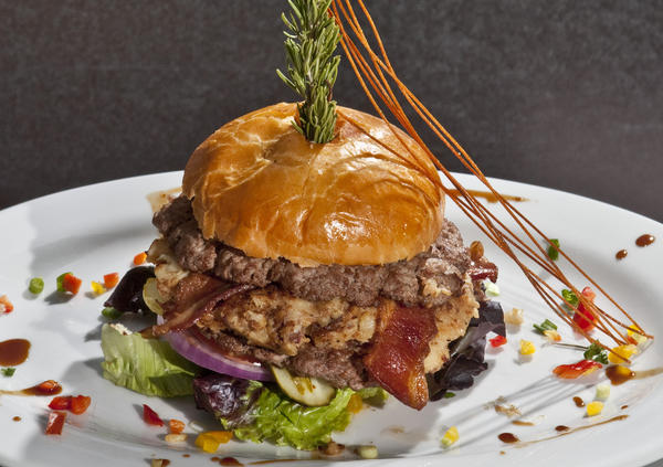 "<i>$12.95 at Hash House A Go Go (1212 N. State Parkway 312-202-0994)</i><br> <b>Toppings:</b> Mashed potatoes and applewood-smoked bacon sandwiched between two patties<br> <b>Weirdness rating:</b> 1. Bacon? Yawn -- but mashed potatoes rack up a point for uniqueness.<br> <b>Messiness rating:</b> 3. Though the mashed potatoes serve as a good glue for the two patties, keeping the whole thing together during consumption is a major feat.<br> <br> Prepare to feel like you're on an episode of ""Man vs. Food"" when this behemoth arrives at the table, secured by a steak knife and a giant branch of rosemary. Size, unfortunately though, is pretty much all this burger has going for it. Though you seemingly can't go wrong with a trifecta of comfort-food goodness (mashed potatoes, bacon and beef) the patties were bland and dry, and the meager slices of bacon got completely lost among everything else. --<i>Tran Ha</i>"