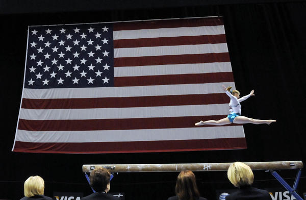Gymnastic judges keep a close eye on Briley Casanova as she performs on the balance beam at the women's senior gymnastics competitors during the 2010 VISA Championships being held at the XL Center