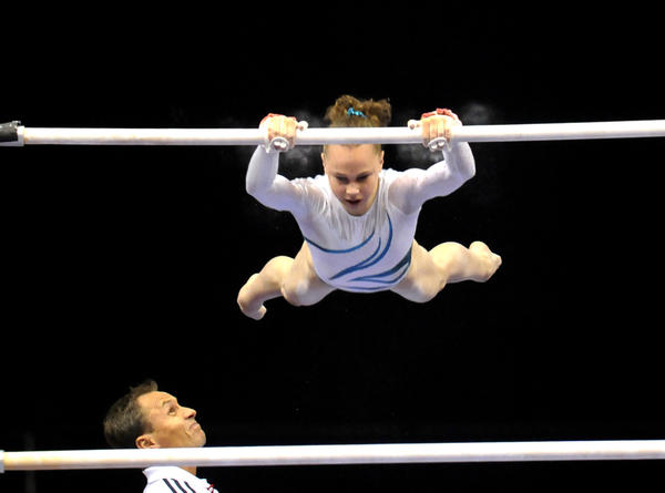 Rebecca Bross gets an approving look form her coach as she performs on the uneven bars during the women's senior gymnastics competiton during the 2010 VISA Gymnastics Championships being held at the XL Center