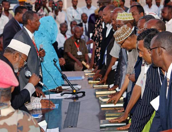 Members of Somalia's new parliament place their hands on copies of the Koran as they take the oath of office in Mogadishu, the capital.