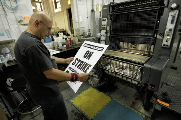 Oscar Moya checks the quality of strike posters being printed Friday at Progress Printing in Chicago for the Chicago Teachers Union.