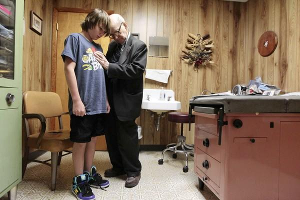 Dr. Russell Dohner, 87, gives Austin Clark, of Macomb, an examination for sports eligibility at his office in Rushville, Ill. Dohner charges only $5 for visits to his office, the same rate he has charged since the 1970s.