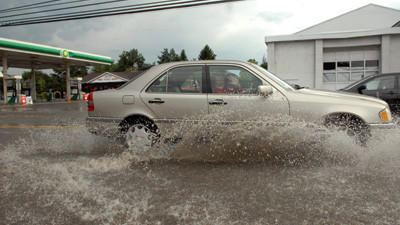 East Main Street in Somerset Borough usually floods during heavy rainfall. Monday's rain burst caused water to again accumulate there. A vehicle is seen traveling through the mire during a storm July 31.