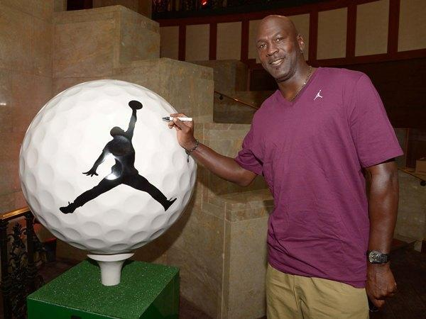 Michael Jordan signs a 3-foot golf ball at Michael Jordan's Steak House August 20, 2012 that will be on display on Michigan Avenue in September.