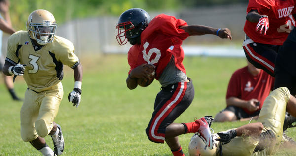 A Dulaney High School player (in red) evades a tackle from an Owings Mills player, leaving him in the dust, and prepares to take another hit.