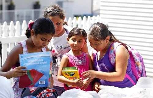 Ashley Flores, Camila Argueta, Kiara Flores and Michele Fidel, left to right, examine each other's school supply choices during an event that donated the supplies and other goods Friday.