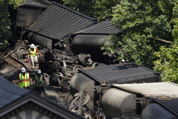 Workers assess the wreckage of an overturned CSX Corp freight train in Ellicott City, Maryland