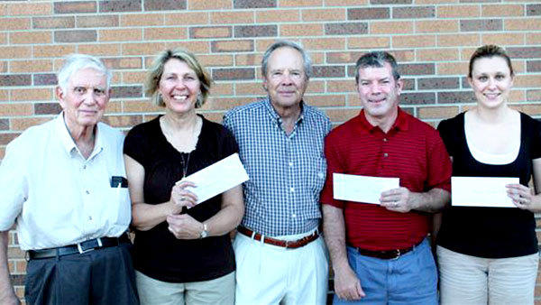 Friends of Music of Lakes of The North representatives Seraphime Mike (left) and Rene Nomforton (second from left) present three area band directors, Rita LaVictoire, Pat Jarve and Jessica Tippett (l-r), each with a $1,000 scholarship check.