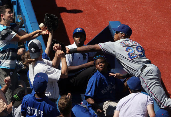 Texas Rangers third baseman Adrian Beltre (29) cannot get to a foul ball as a fan reaches out for a pop up in the sixth inning against the Toronto Blue Jays at the Rogers Centre. The Rangers beat the Blue Jays 2-1.