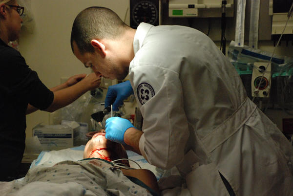 "Chief resident Lucas Rosier inspects the stitches of a patient at Stroger Hospital in a scene from ""Chicago Trauma."""