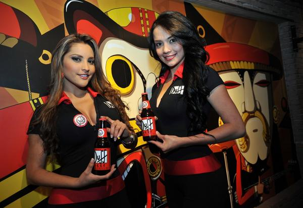 Promoters show Duff beers during an event on August 17, 2012, at a bar in Bogota, Colombia. Two Colombian entrepreneurs are waging a court battle in Bogota to continue producing the beer inspired by the animated series The Simpsons.