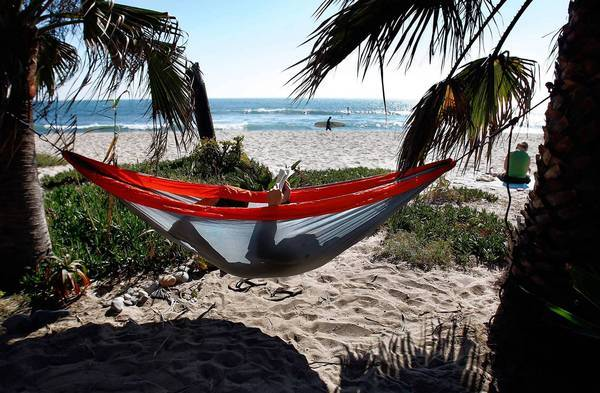 Sixty-six percent of people who plan to travel over the Labor Day weekend said their current financial situation would not negatively affect their travel plans. Above, a man reads a book while relaxing in a hammock at San Onofre State Beach during the 2010 Labor Day weekend.