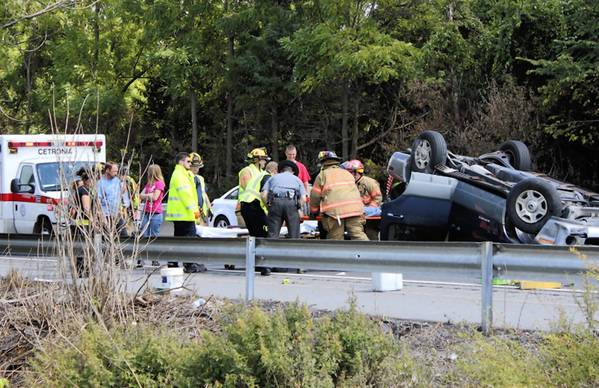 Emergency workers tend to a driver injured Tuesday afternoon when his sport utility vehicle flipped on Route 22 westbound in South Whitehall Township. Officials have not disclosed the man's condition.