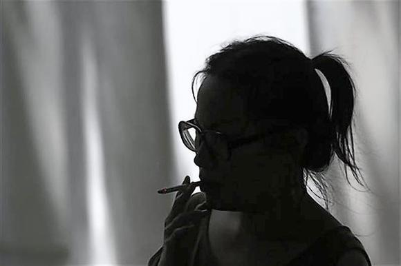 A woman smokes a cigarette