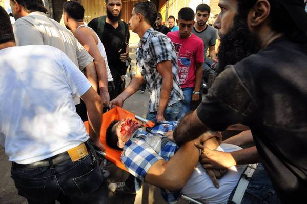 An injured man is carried away in Tripoli, Lebanon, after clashes between opponents and supporters of Syrian President Bashar Assad.