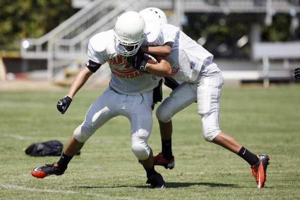 Pasadena Poly's Griffin Carter, left, is tackled by Curtis Toyota during practice at Pasadena Poly on Saturday. (Cheryl A. Guerrero/Staff Photographer)