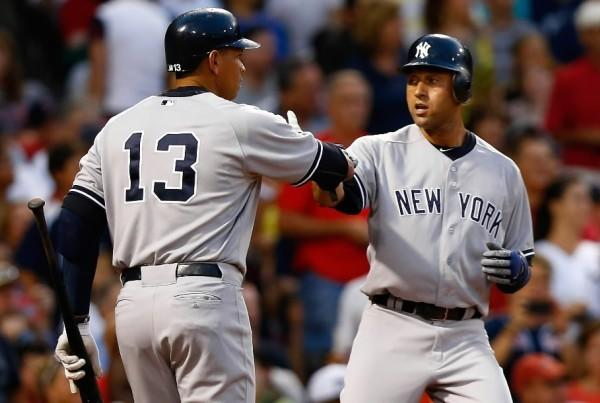 Derek Jeter (right) is congratulated by New York Yankees teammate Alex Rodriguez (right) after scoring against the Boston Red Sox July 8, 2012 at Fenway Park in Boston.