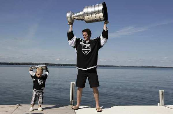 Kings center Colin Fraser and son Calder, 18 mos., hoist Stanley Cups together on the banks of Sylvan Lake in Canada.