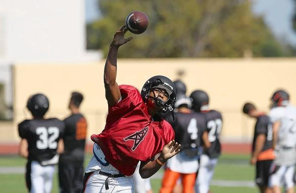 Huntington Beach High quarterback Kai Ross throws a pass during practice on Monday.