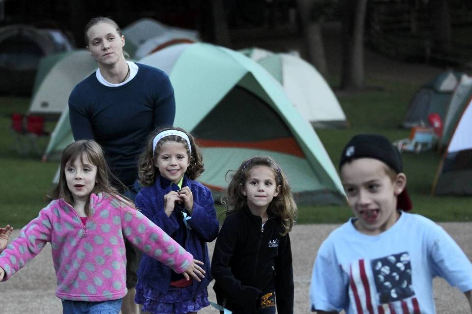 Children run from the tent area as they frolic around Lincoln Park Zoo during an overnight camping experience.