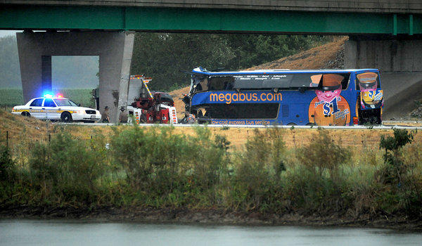 Illinois State Police and emergency personnel prepare to remove a Megabus interstate bus that struck an overpass on I-55 five miles north of Litchfield, Ill.