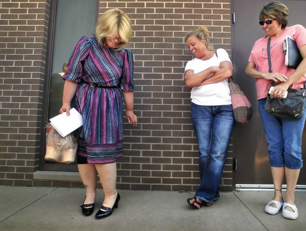 Kristine Bunch, left, admires shoes her mother gave her to wear after her release Wednesday in Greensburg, Ind. Friends with a prison ministry, right, greeted her.