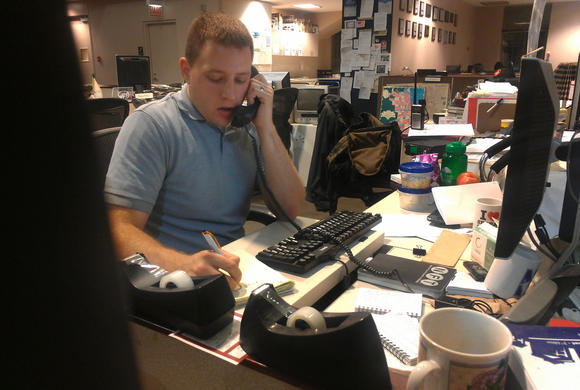 Peter Nickeas works the phones during the overnight Breaking News shift.