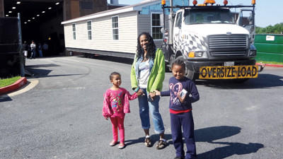 Kim Johnson and her daughters Anisa and Sidney stand in front of a section of their new home being moved from Harford Tech.