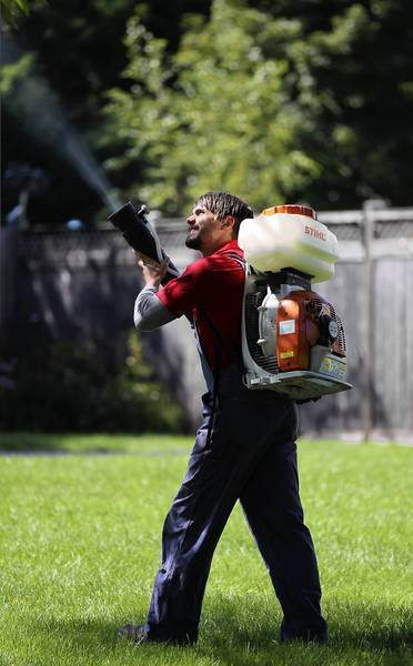 Brad Hunt, a technician with Skeeter Beaters, sprays mosquito repellant in Glenview on Tuesday. State and federal officials are reporting a substantial increase in the number of reported cases of West Nile virus over last year.