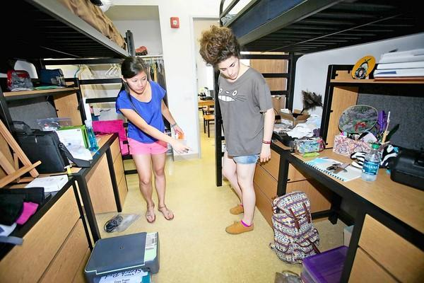 Freshmen Mary Dinh, 18, left, of Louisiana, and roommate Emma-Claire Krikorian, 17, right, of Thousand Oaks, acquaint themselves with their dorm room at Laguna College of Art and Design on Saturday.