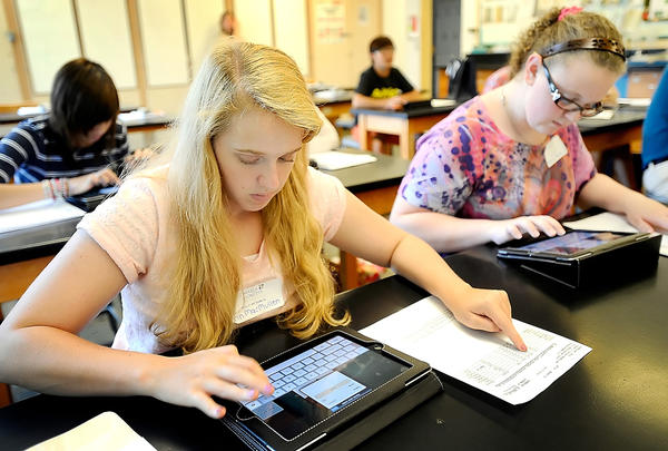 Erin MacMullen, left, an incoming St. Maria Goretti freshman from Frederick, Md., finds her way around her new iPad Thursday afternoon during freshman orientation. At right is freshman Sierra Moore of Funkstown.