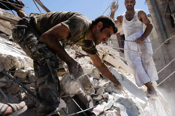 Syrians in Aleppo try to remove the body of a man buried under the rubble of a building bombed by a warplane.