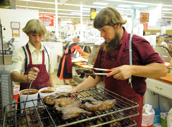 Jake Beiler, left, and Leroy Stoltzfus, of Beiler's Bar-B-Que in the Joppatowne Plaza farmers' market, prepare boneless beef and short ribs.