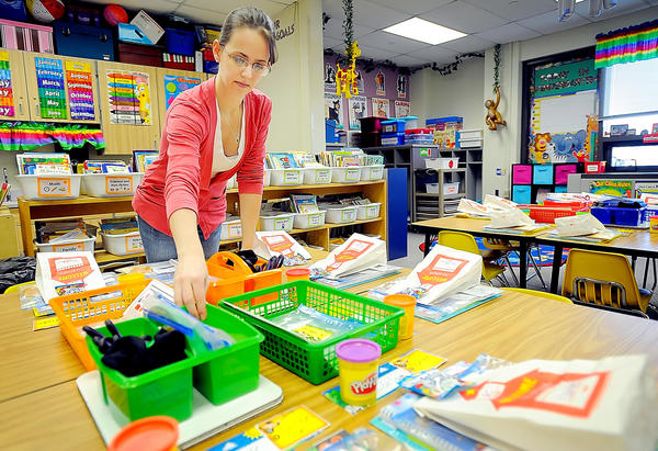 Justine Gibbon, a fourth year Kindergarten teacher at Greencastle-Antrin Primary School, sets up the desks for her students who will be arriving next Monday for the first day of school.