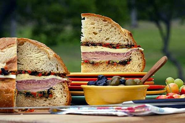 Layer cured meats, provolone and an olive-vegetable relish on a large, round loaf to make a substantial and satisfying muffuletta.