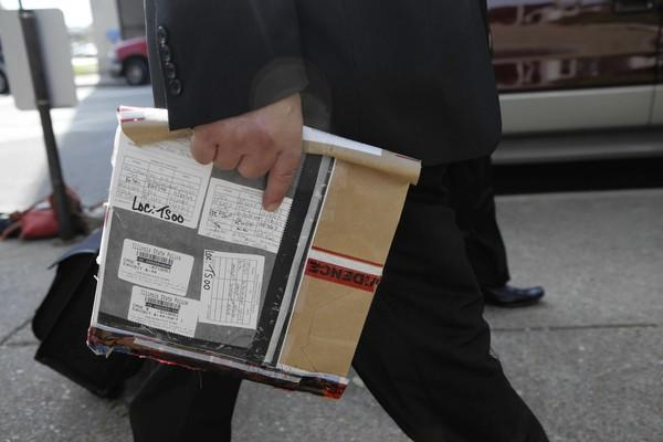 A prosecution team member carries a folder Thursday with receipts that authorities say Drew Peterson kept so he could later use them to support an alibi.