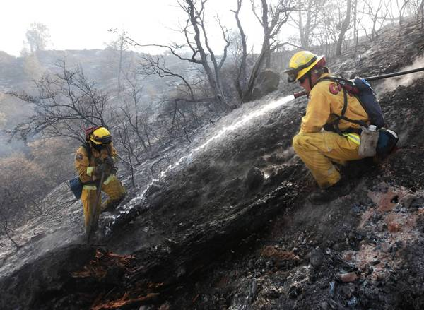 Firefighter Dennis Navle, right, hoses down a smoking log as he and Robert Smith work hot spots of the Ponderosa fire Thursday.