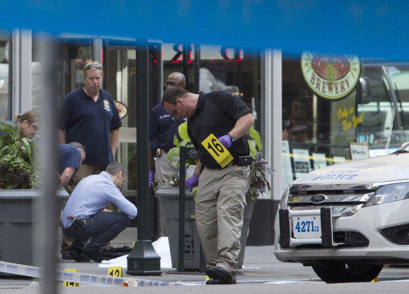Law enforcement stands near the covered body of a suspected shooter on 5th Ave. near the Empire State Building August 24, 2012 in New York City.
