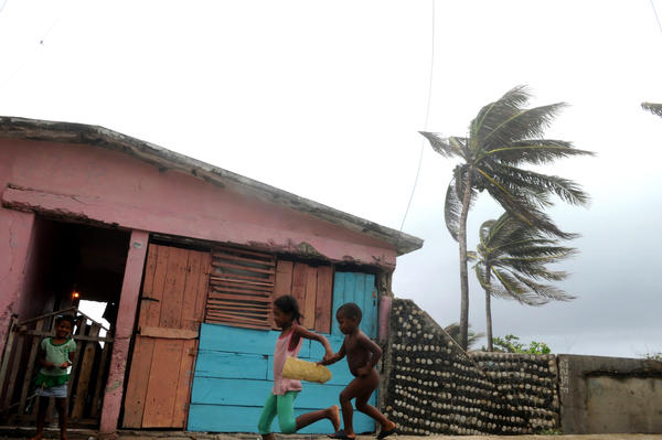 Children run for shelter at the Bahoruco beach in Barahona, Dominican Republic August 24, 2012, where the strong swell announces the arrival of Tropical Storm Isaac.