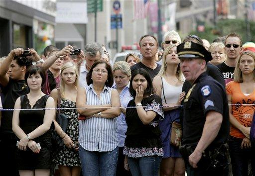 Bystanders and a police officer stand on Fifth Avenue in New York CIty to view the scene after a multiple shooting outside the Empire State Building on Friday.