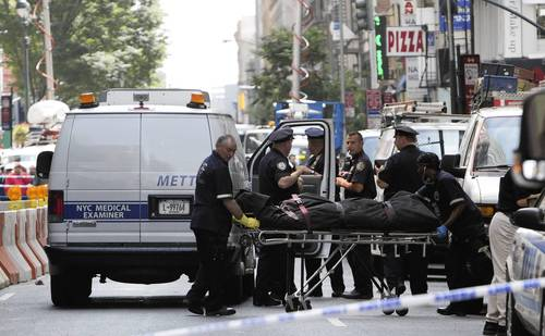 The body of a shooting victim is wheeled to a medical examiner's van on West 33rd Street after being killed by 58-year-old Jeffery Johnson near the Empire State Building in New York City. Police said Johnson shot and killed a 41-year-old former co-worker of Hazan Imports during an altercation at 10 W. 33rd St. with a .45 caliber handgun.