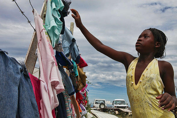 Francois Romerose, 11, brings in laundry at the Fondation Montesinos orphanage in Titanyen, Haiti, where Food For The Poor is building a dormitory and a school. Residents were preparing for Tropical Storm Isaac on Friday Aug. 24, 2012.