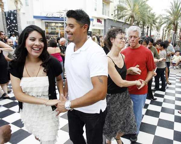 Nathaly Rafton and Jason Salinas, who are dance friends, learn how to salsa dance at the ninth annual 'Come Out and Dance Under the Stars' in Burbank.