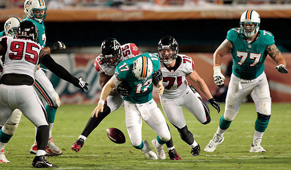 Miami Dolphins quarterback Ryan Tannehill (17) is tackled by Atlanta Falcons defensive end Kroy Biermann (71) and defensive end John Abraham (55) causing in a fumble in the second quarter at Sun Life Stadium.
