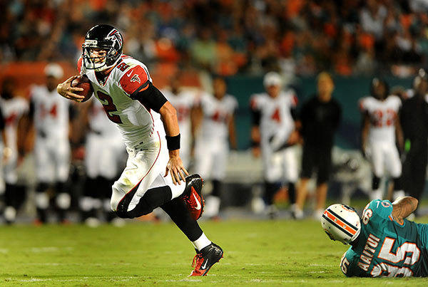 In the second quarter, Atlanta quarterback Matt Ryan escapes the grip of Dolphin's defensive tackle Isaako Aaitui as Ryan heads deep into Miami territory.