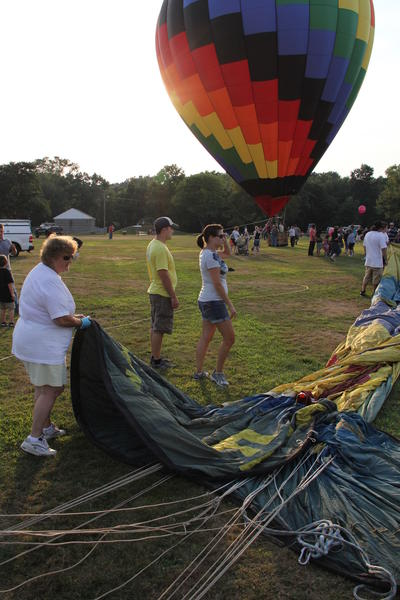 Crew members of Adventure Balloons of Plymouth, Conn., unfold the balloon Party Time at the Plainville balloon Festival Friday evening.