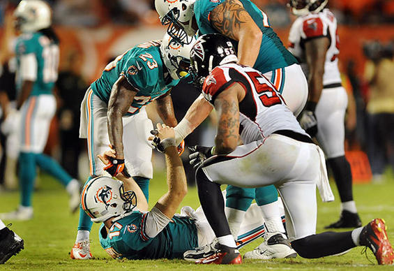 Dolphin's quarterback Ryan Tannehill needs help getting up from teammates Steve Slaton at left and Jake Long at center after being hit hard while throwing.