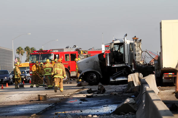 Burbank firefighters respond to a crash on the 5 Freeway at Hollywood Way where a big rig collided into the center divider Friday, causing diesel fuel to spill across lanes on both sides of the freeway.