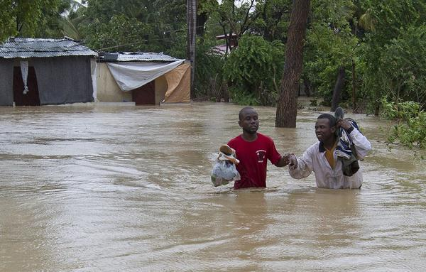 Residents of a low lying area in Port au Prince flee their flooded homes with their possessions August 25, 2012. Tropical Storm Isaac emerged over warm Caribbean waters on Saturday slightly weaker but ready to regroup after dumping torrential rains on Haiti, where thousands of people remain homeless more than two years after a devastating earthquake.